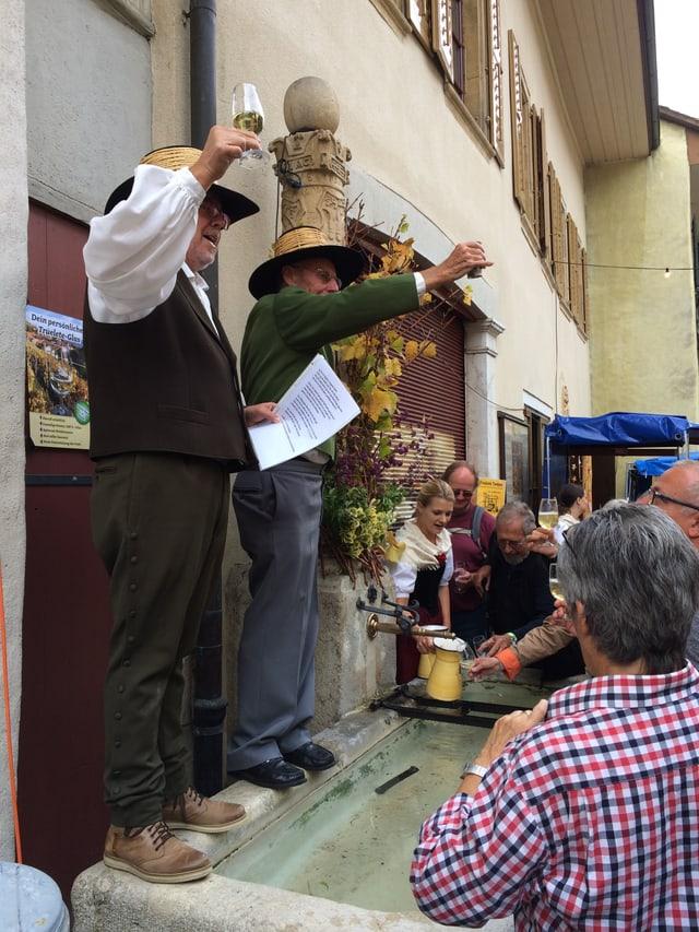 Zwei Männer stehen auf dem Brunnenrand und erheben die Gläser.