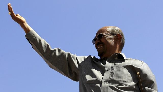 al-Baschir mit Sonnenbrille und erhobener Hand vor blauem Himmel.