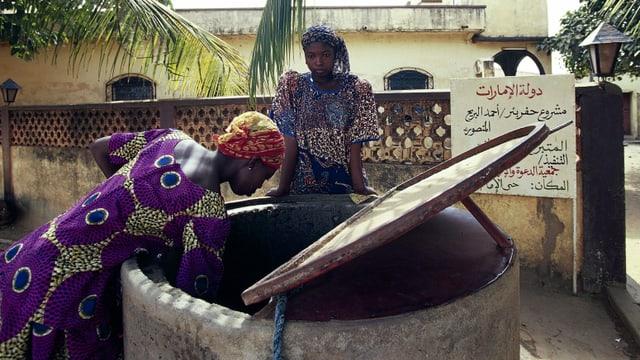 Zwei Frauen an einem Brunnen.
