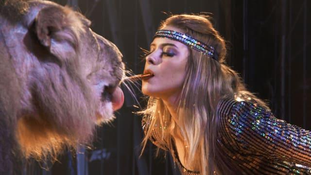 Eine Frau hält ein Stück im Mund, das ein Tiger abschleckt.