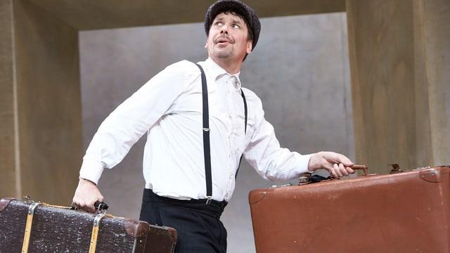 Ein Mann mit weissem Hemd und schwarzen Hosenträgern trägt zwei Koffer über die Bühne.