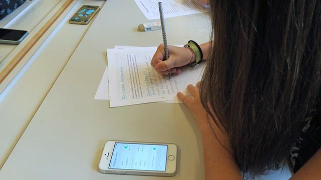 Ein Mädchen mit langen Haaren schreibt Schularbeiten auf dem Tisch liegt ein Handy.