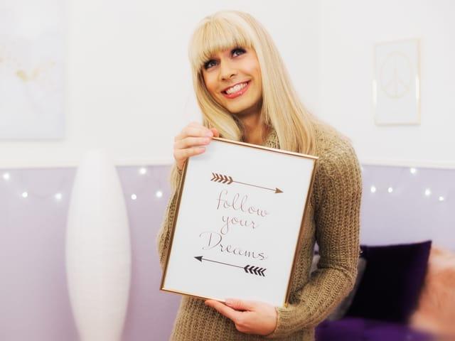 """Jenny-Wanessa in ihrem Wohnzimmer. In der Hand hält sie ein eingerahmtes Bild. Darauf ist zu lesen: """"Follow your Dreams"""""""