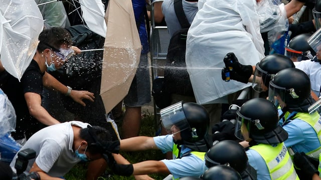 Polizisten gehen mit Pfefferspray gegen Demonstranten vor, die sich mit Regenschirmen wehren.