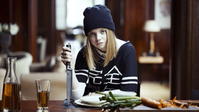 Die Filmtochter Winnie sitzt mit einem grossen Gemüsemesser am Tisch und sticht die Klinge in den Tisch. Dabei sieht sie sehr gelangweilt aus.