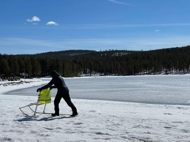 Mann mit Schlitten im Schnee