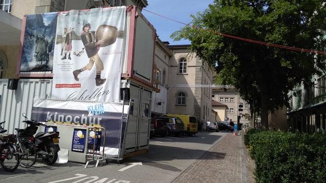 La Via da Teater, davant il container cun in placat dad Ursin, davos autos sin il parcadi sper via.