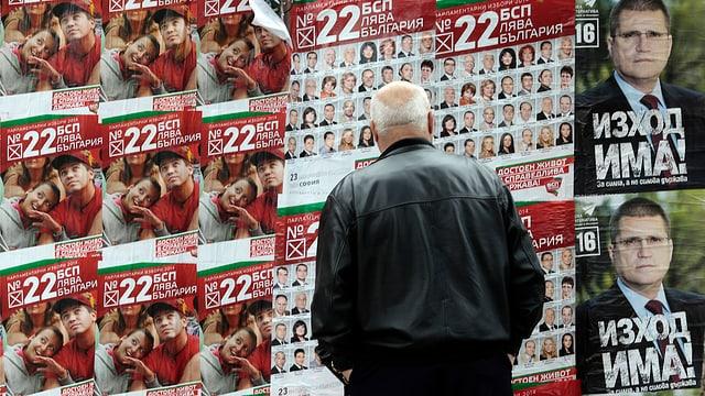 Ein Mann steht vor einer Wann mit vielen Wahltransparenten.