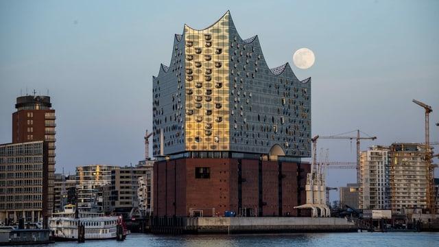Grosses gläsernes Gebäude auf hohem Backstein-Sockel, Vollmond im Hintergrund