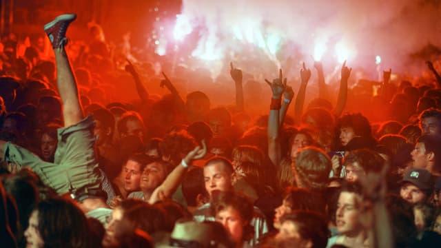 Ein Mann springt an einem Rockkonzert kopfüber in die Menge.
