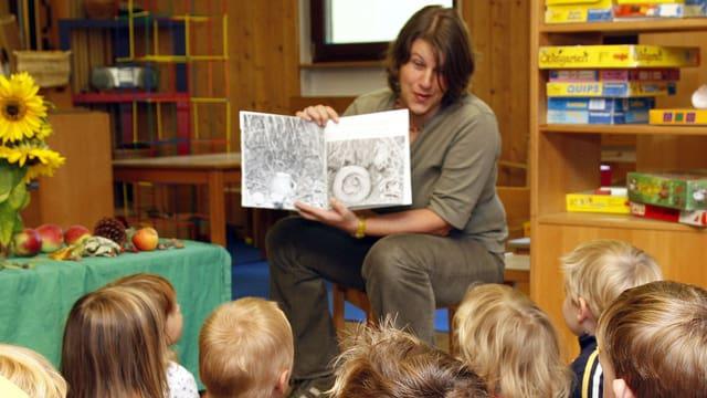 Eine Frau liest Kindern aus einem Buch vor.