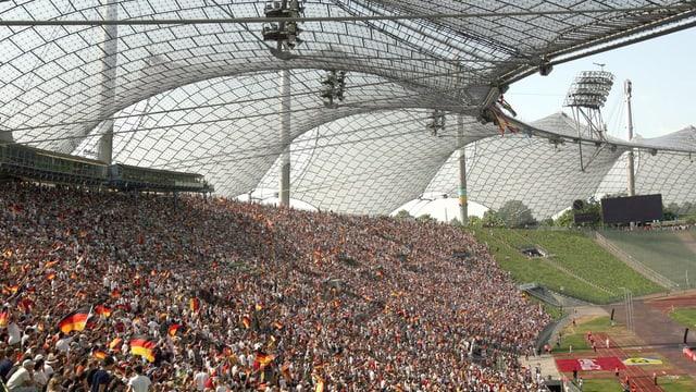 Ein zeltartiges Dach des Olympiastadions in München, Fans auf der Tribüne.