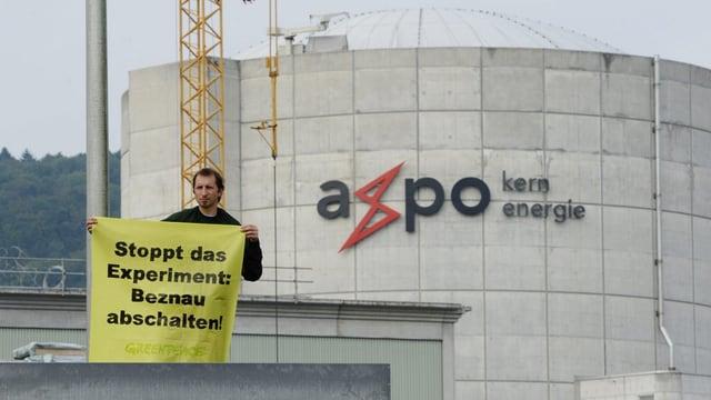Greenpeace-Aktivist mit Protest-Plakat vor dem AKW Beznau