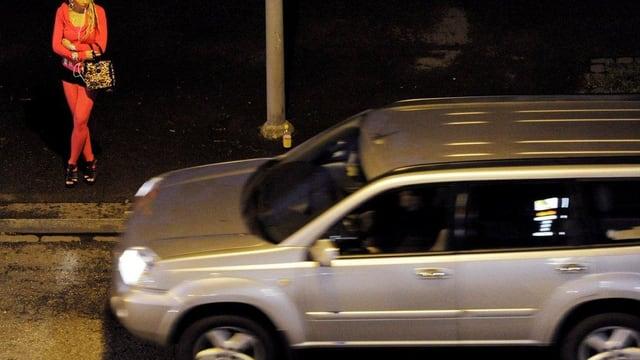 Ein Auto fährt an einer Sexarbeiterin vorbei.