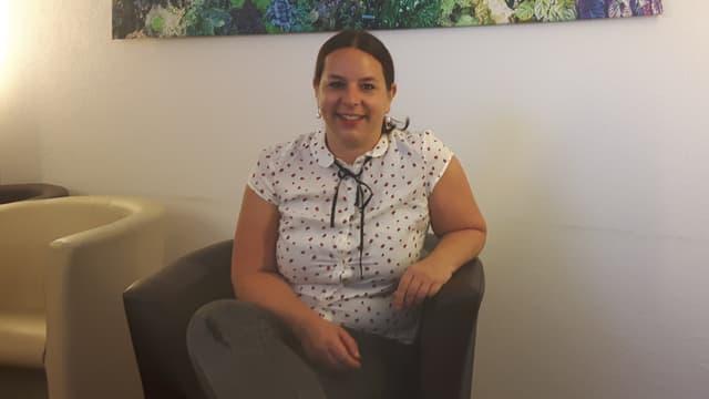 Eine Frau, welche auf einem Stuhl sitzt.