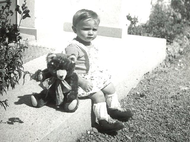 Junge mit Teddybär auf Treppenstufe.