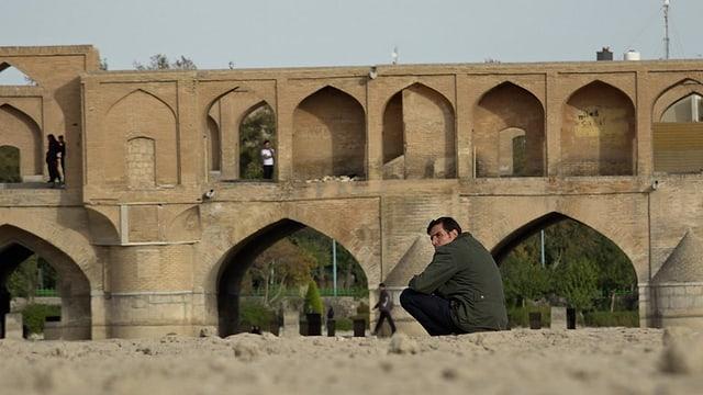 Mann sitzt in Isfahan, Iran in der Nähe einer Brücke.