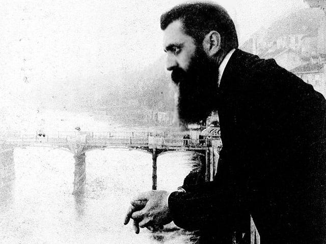 Ein Mann mit Bart steht auf dem Balkon am Rhein und schaut in die Ferne.