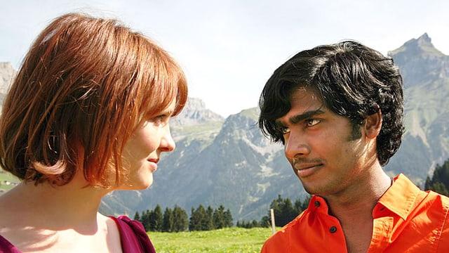 Leo und Devan stehen vor einem Bergpanorama und schauen sich in die Augen.