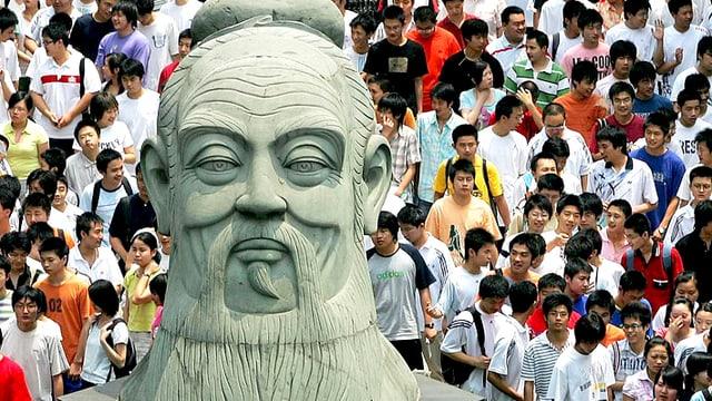 Junge Chinesen gehen an einer riesigen Büste von Konfuzius vorbei.