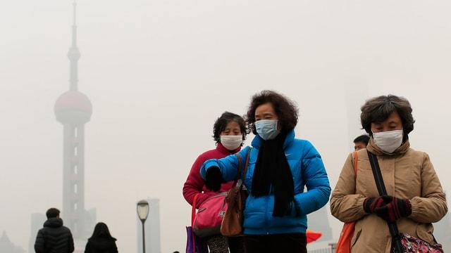 Trais dunnas asiaticas portan mascras alvas sur la bucca, davos as vesa in bajetg en il smog.
