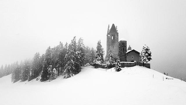 Blick auf die verschneite Landschaft bei Celerina mt einer Kirchenruine.