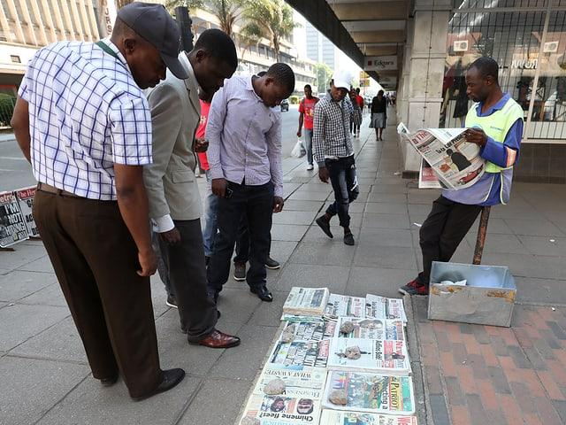 Männer schauen am Boden liegende Zeitungen an.