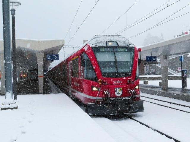 Die Bahn steht am Bahnhof in St. Moritz, es schneit.