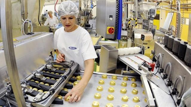 Eine Arbeiterin von Hero in Lenzburg kontrolliert Konfitüren-Portionen.