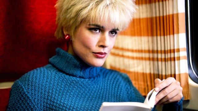 Eine Frau mit kurzem, wasserstoffblondem Haar, rot geschminkten Lippen und einem Rollkragenpullover liest ein Buch in einem Zug.