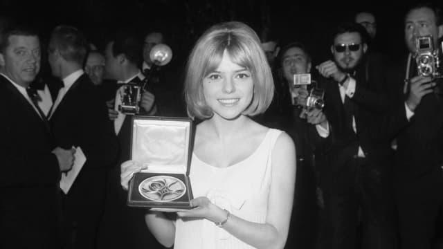 Auf dem Bild ist France Gall zu sehen mit dem Eurovision Song Contest Award in ihrer Hand. Hinter ihr Paparazzi.