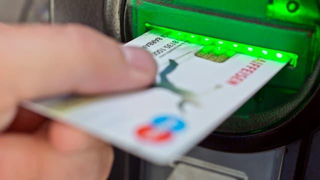 Bankkarte wird in einen Automatenschlitz geschoben.