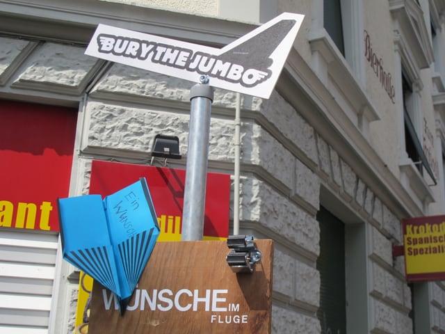 """Ein Ständer mit einem blauen Papierflugzeug, darüber das Logo von """"Bury the Jumbo"""" mit einem Flugzeug."""