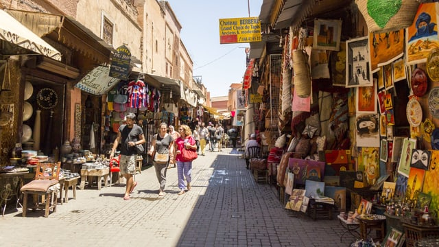 Touristen schlendern durch einen Souk in einer maghrebinischen Stadt.