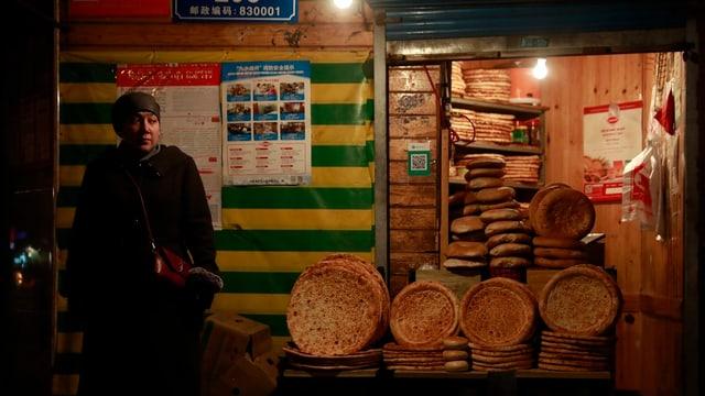 Eine Frau steht neben aufgestapelten Nan-Broten.