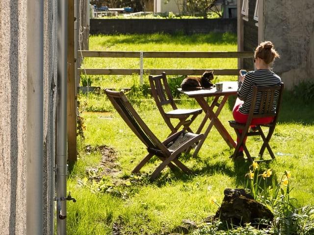 Eine Frau sitzt im Garten und schaut auf ihr Smartphone. Auf dem Tisch sitzt eine Katze.