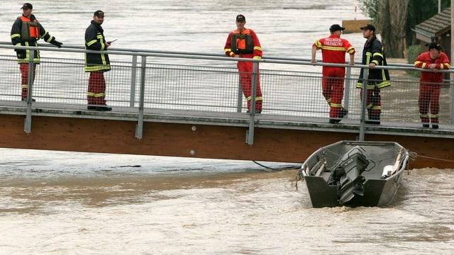 Feuerwehrleute beobachten auf einer Brücke das Hochwasser in Mellingen 2005.