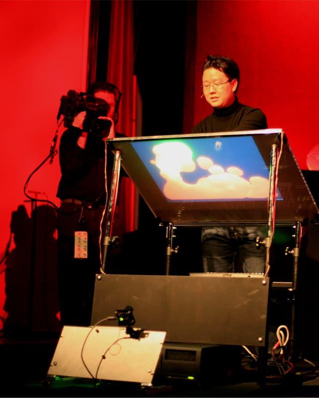 Asiatisch stämmiger Mann vor dem Prototypen eines Touchscreens.