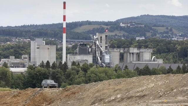 Brauner Hügel im Vordergrund, Fabrik im Hintergrund.