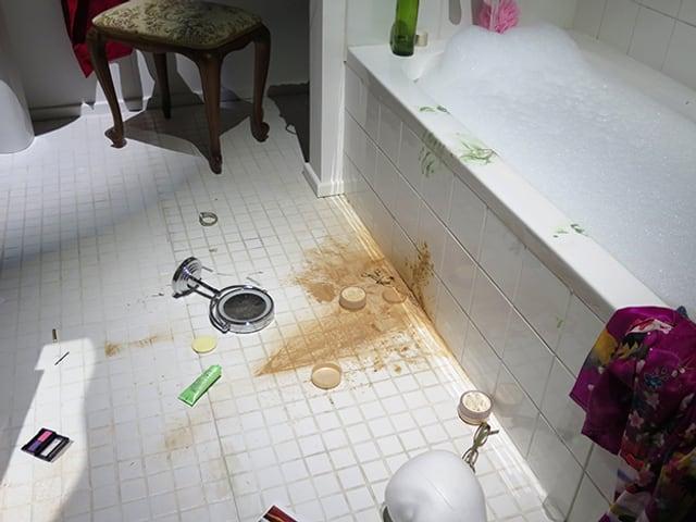 Kaputte Puderdose auf einem Badezimmerboden.