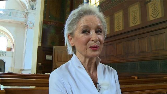 Heidi Maria Glössner sitzend in einer Kirche.
