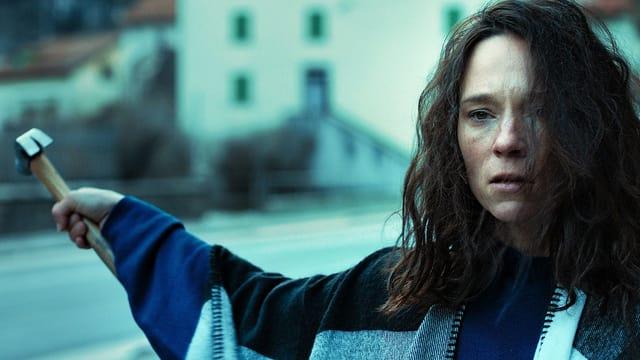 Eine Frau hält einen Hammer in der Hand. Sie sieht etwas verstört aus, ihr Haar ist zerzaust. Sie steht draussen an einer Strasse.