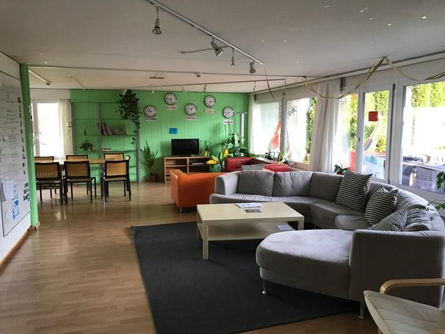 Ein Wohnzimmer mit grauem Sofa, einem Esstisch mit Stühlen und hinten eine Wand mit Uhren, welche alle verschiedene Zeitzonen anzeigen.