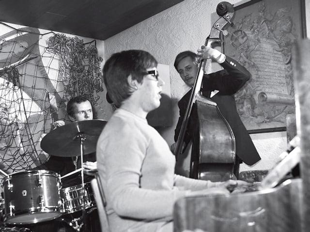 Ein Schlagzeuger, eine Frau am Piano und ein Mann am Kontrabass in einem Raum.
