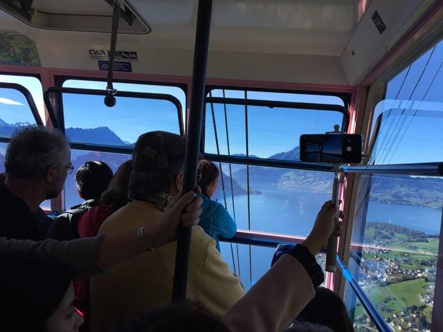 Seilbahnpassagiere blicken hinunter auf den Vierwaldtstättersee