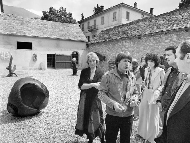 Eine Personengruppe vor einem Steinhaus.