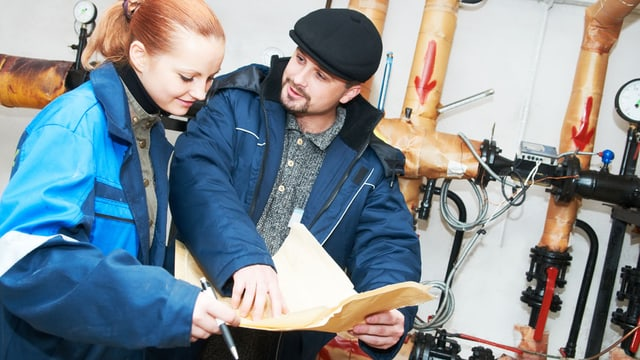 Ein Handwerker erklärt einer Hausbesitzerin im Heizungskeller auf einem Papier das Vorgehen.