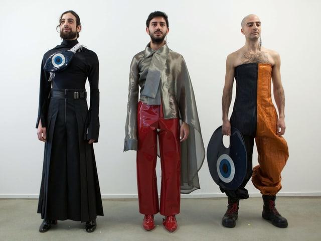 Drei Männer in bunten Kleidern mit Taschen