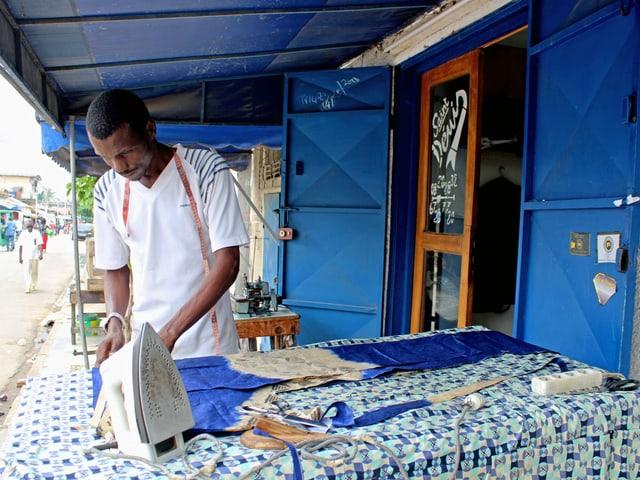 Vor einer Schneiderei bügelt ein Mann ein Kleid