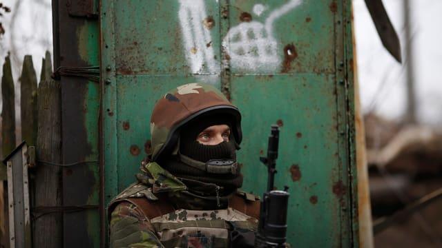 Soldat mit Gesichtsmaske und Gewehr.